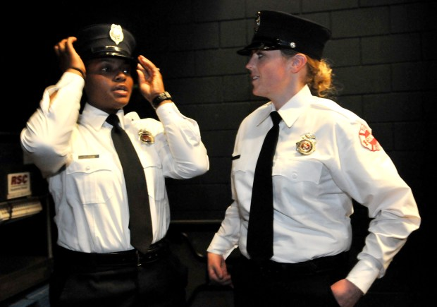 Brittney Baker, left, adjusts her new hat as her classmate, Kayla Sanchez, waits with her backstage after 19 new St. Paul firefighters graduated from the city's Firefighter Academy during a ceremony at the Paul and Sheila Wellstone Center in St. Paul on Friday, May 11, 2018. (Ginger Pinson / Pioneer Press)
