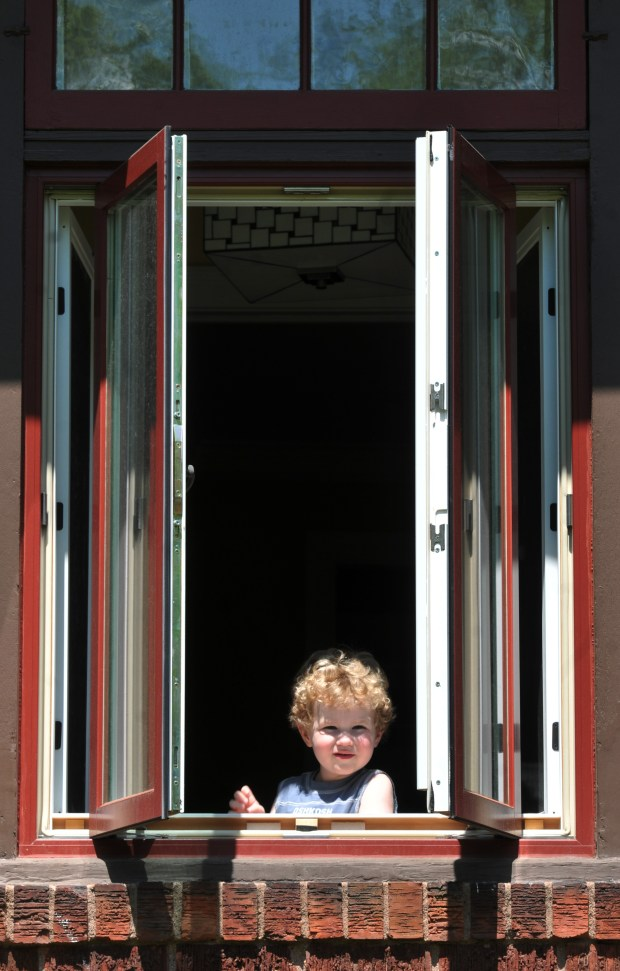 Kyle Caucutt, 3, looks out of a casement window on his parents Summit Ave. home on Wednesday, May 17, 2018. The Caucutt's who live on Summit Ave. in St. Paul wanted to replace nine pairs of interior swinging window casements in 2014 that had caused high heating bills, security concerns and cuts and bruises for their children who ran into them as they arced inward with each hard wind. The replacement windows were to be customed ordered. Initially the city's Heritage Preservation Commission rejected their request saying the proposal was a threat to the their homes historic architecture. Wendy appealed the decision to the city of St. Paul City Council which unanimously agreed to reverse the decision in her favor. (Ginger Pinson / Pioneer Press)
