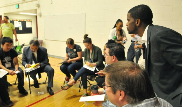 After delivering his State of the City address, St. Paul Mayor Melvin Carter leans over to better hear the discussion going in the gym at Johnson Senior High during a breakout session around minimum wage with the opportunity for St. Paul citizens to engage in small group discussions to provide feedback and solutions for Saint Paul. (Ginger Pinson / Pioneer Press)