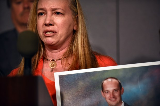 Danielle Wishard-Tudor holds a picture of her brother, Jean-Claude Wishard, as she speaks to reporters in support of a hands-free driving proposal at the State Capitol in St. Paul Thursday, May 10, 2018. Jean-Claude Wishard, of Belle Plaine, Minn., was killed Oct. 29 in a distracted-driving crash in Minnetrista. (Dave Orrick / Pioneer Press)