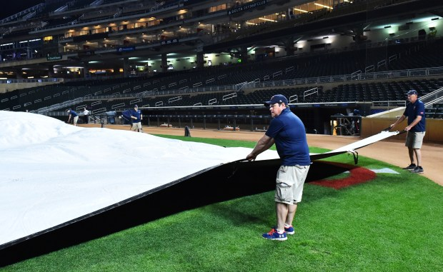 Pioneer Press sport reporter Brian Murphy helps Target Field assistant grounds keeper Al Kuehner hold the tarp taut after the grounds crew unrolled to cover the infield in anticipation of rain after the Minnesota game against Milwaukee at Target Field on Friday May 18, 2018. (John Autey / Pioneer Press)
