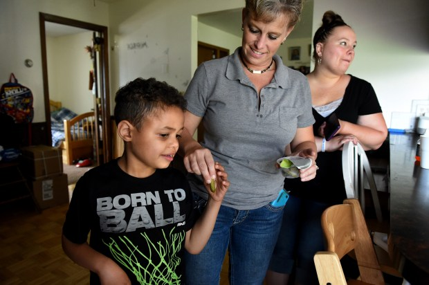 Cedarius Nanoff gets a pickle from his grandmother, Cindy Nanoff, for an afternoon snack as she visits in Hastings Wednesday, June 20, 2018. His mother, Stacie Nanoff, is at right. (Jean Pieri / Pioneer Press)