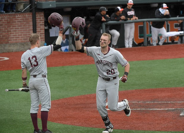 Minnesota's Toby Hanson (20) taps helmets with Luke Pettersen (13) after Hanson hit a solo home run off Oregon State's Luke Heimlich during the opening game of an NCAA college baseball tournament super regional in Corvallis, Ore., Friday, June 8, 2018. (Mark Ylen/Albany Democrat-Herald via AP)