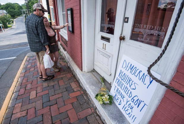 "Passersby examine the menu at the Red Hen Restaurant Saturday, June 23, 2018, in Lexington, Va. White House press secretary Sarah Huckabee Sanders said Saturday in a tweet that she was booted from the Virginia restaurant because she works for President Donald Trump. Sanders said she was told by the owner of The Red Hen that she had to ""leave because I work for @POTUS and I politely left."" (AP Photo/Daniel Lin)/Daily News-Record via AP)"