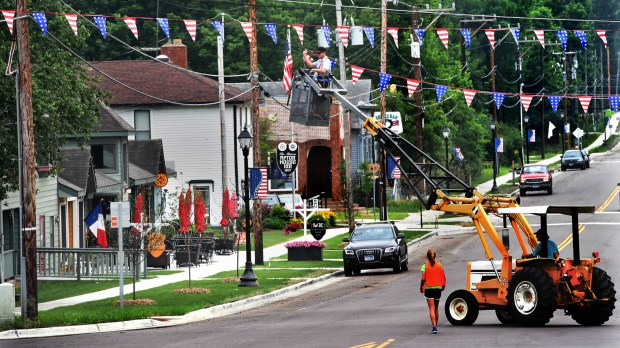 Noah Driscoll from Windmill Marina helps string flags in Afton's Old Village on June 27, 2018, in preparation for the town's annual Fourth of July parade. Four major infrastructure projects -- a community sewer system, an improved flood levee, a new stormwater system and reconstruction of St. Croix Trail and side roads -- were recently completed after years of planning and construction. (Jean Pieri / Pioneer Press)