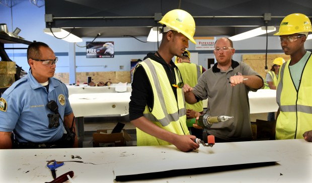 Como Park Senior High school resource officer, Toy Vixayvong, left, and Andrew Richmond, third from left, Apprentice Coordinator at Roofers & Waterproofers Apprenticeship Training Facility Local 96 in Blaine, help and teach students on Thursday, June 28, 2018. Vixayvong partnered with the Minnesota Trade Academy to place Como Park students and recent graduates in paid trade internships for the summer. (Jean Pieri / Pioneer Press)