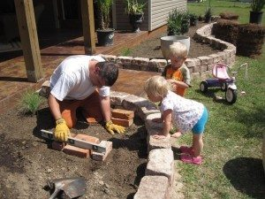 Jean L. and twins build a garden.