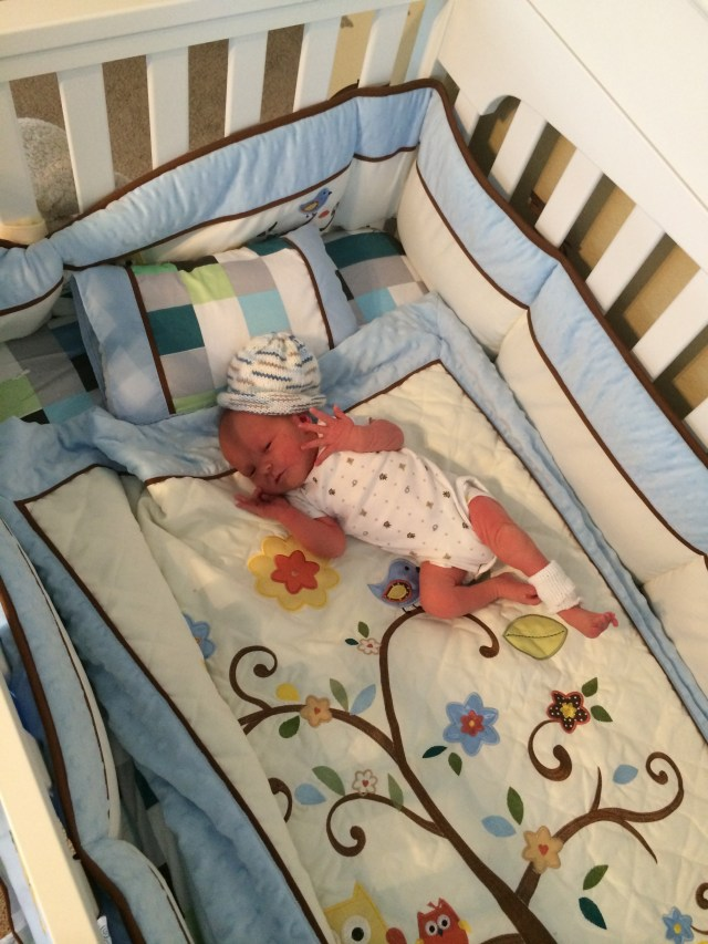 Tiny baby in a huge crib