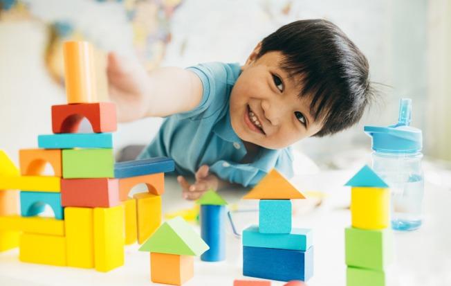 Boy toddler playing with blocks.