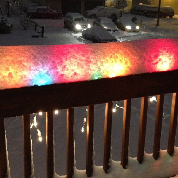 Christmas lights glowing under the snow.