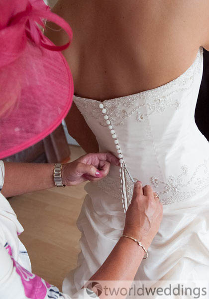 Mother putting on a wedding dress captured by all inclusive wedding photographers,make up artists and hairstylists TWorld Weddings Staffordshire Uk and destination weddings.