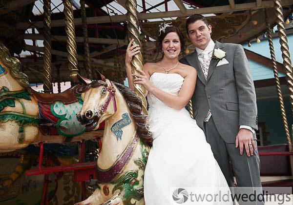 Bride and grrom on a carousel on their wedding day having wedding photos taken.