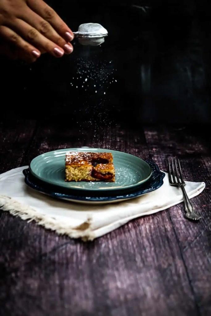piece of plum sheet cake on a light green plate.