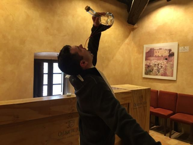 "Russell drinking wine from the porron. Luckily he wore a bib! - ""Montserrat: Mountain, Monastery, and Wine"" - Two Traveling Texans"