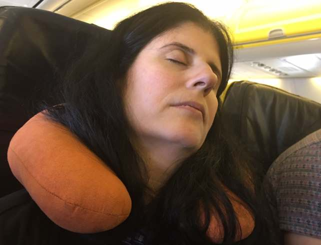 """Anisa using her neck support pillow to help get some sleep on a flight. - """"Neck Support Pillow and Other Travel Sleeping Tips"""" - Two Traveling Texans"""