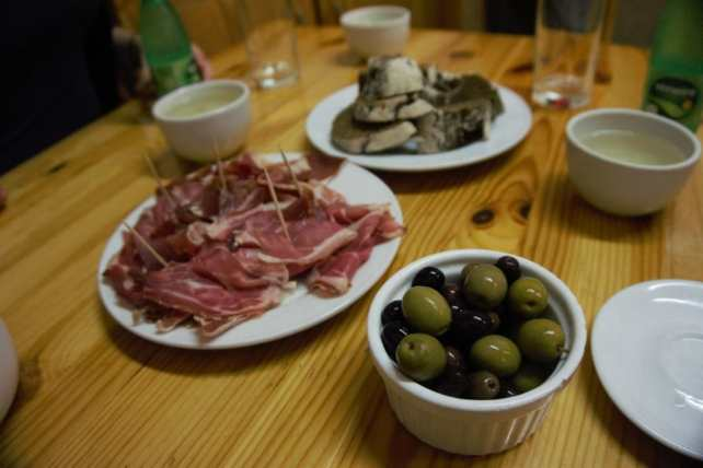 """Olives, ham, and the brown corn bread with more Vinho Verde served in ceramic cups. - """"Porto Food Tour: Taste the Local Specialties"""" - Two Traveling Texans"""