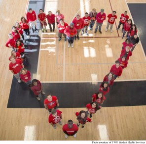 TWU Pioneers on the Denton campus pose together to show support and raise awareness for Go Red for Women.