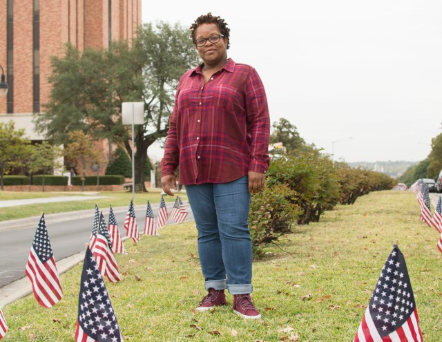 Student Veterans Association President Nikki Perez stands amongst a flag display created by student-veterans along Bell Avenue.