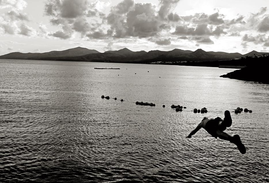 Un niño se lanza en agua en Playa Chica. Puerto del Carmen.