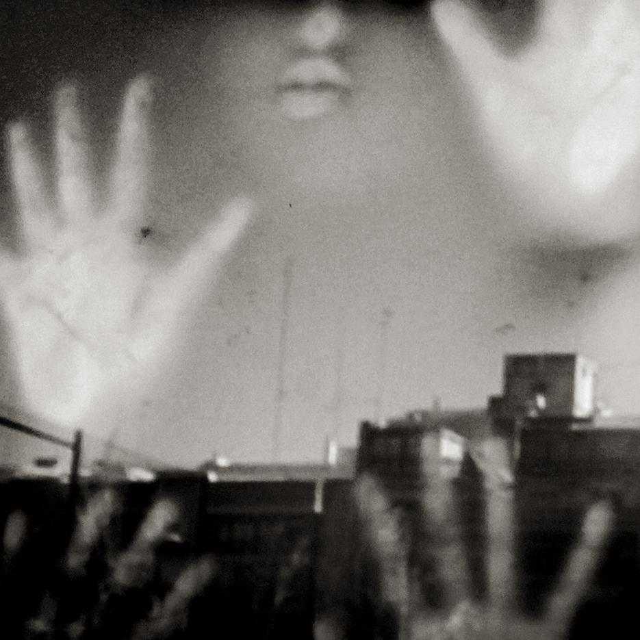 Manos y rostro tras la ventana en un centro para mujeres que han sufrido malos. Valencia. tratos