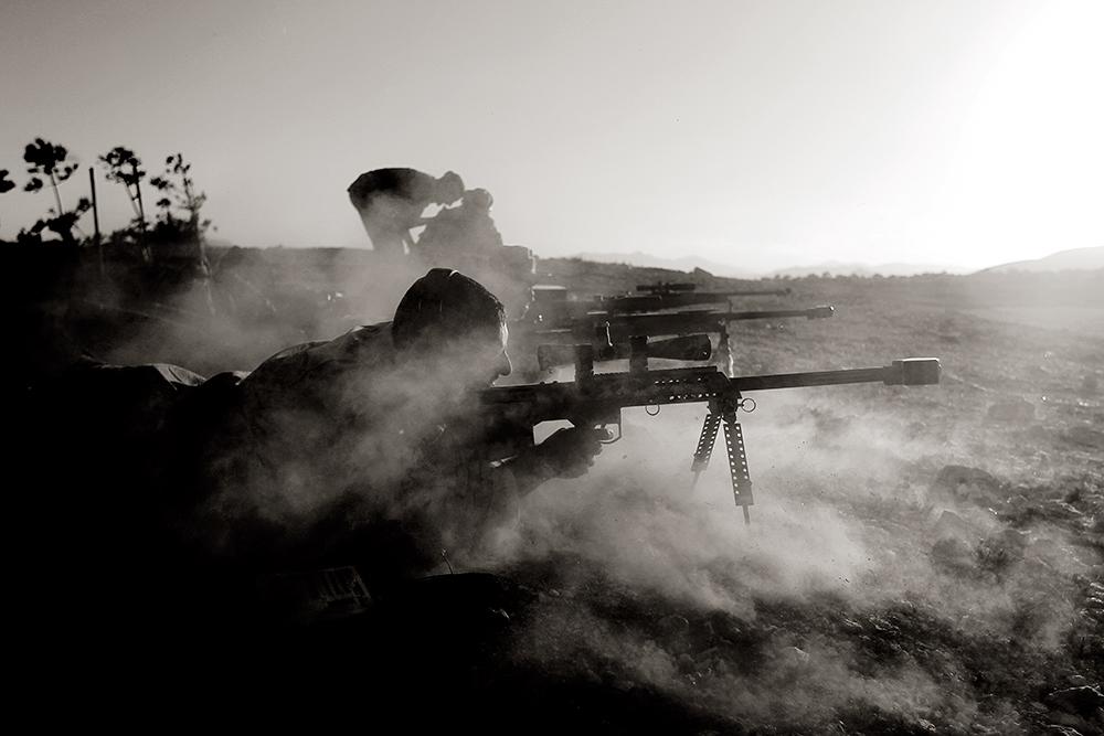 El disparo de un fusil de largo alcance hace temblar la tierra y levanta una nube de polvo.