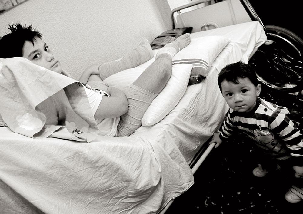 David, y a los pies de la cama su hermano pequeño, Iván, que tiene catorce meses de edad. En aquel momento, septiembre de 2012, David  llevaba cuatro meses en la cama, desde que el cirujano Pedro Cavadas le reimplantó los pies que había perdido en un accidente de tráfico. Sus padres, David (camarero) y Mari Trini (ayudante de cocina), de Granada,  vivían en Manises, cerca de Valencia, al lado del hospital. Dejaron de trabajar, no podían pagar el alquiler y el banco había comenzado el proceso de embargo del piso viejo que habían comprado y que en cinco años habían logrado arreglar. Iban a irse a vivir allí ese año.