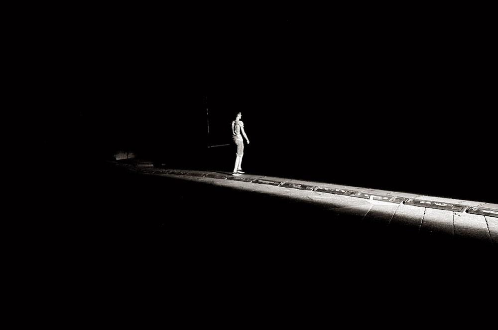 """En la Plaza Mayor de Bolonia proyectan en una pantalla grande """"La tragedia di un uomo ridicolo"""". El haz de luz muestra por dónde pasan los cables de la luz para la proyección."""