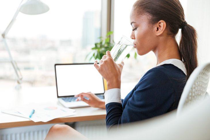 African businesswoman drinking water | Introducing Your Body To Alkaline Water | alkaline water benefits