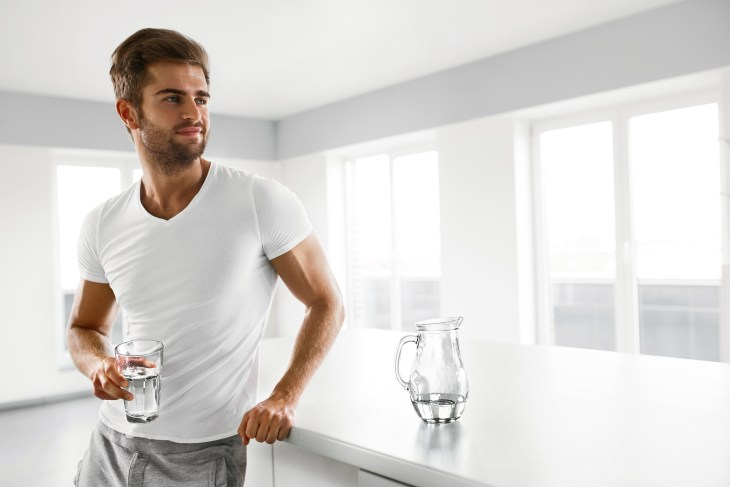 Healthy Nutrition. Man Drinking Glass Of Fresh Water In Morning
