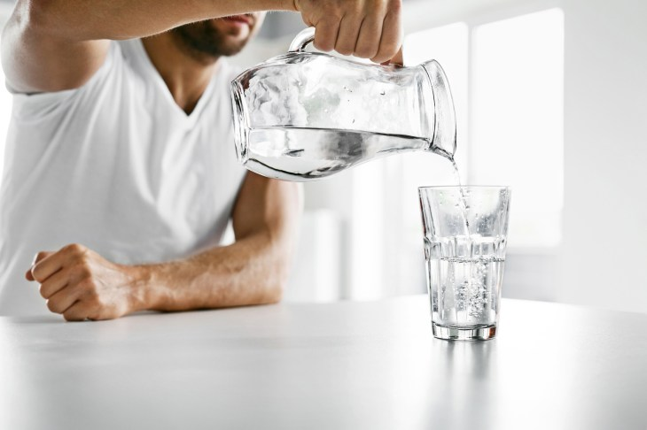 Drink Water. Close Up Man Pouring Water Into Glass. Hydration
