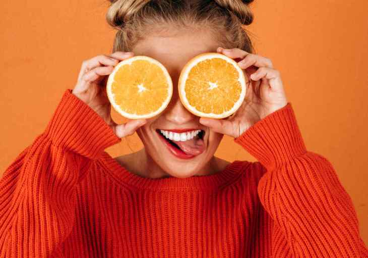 Lady holding a sliced Oranges | Fruits and Veggies That Can Keep You Hydrated