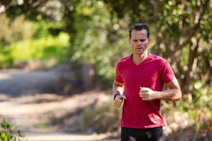 Man running on path surrounded with trees | What Is Alkaline Water? | What You Need To Know
