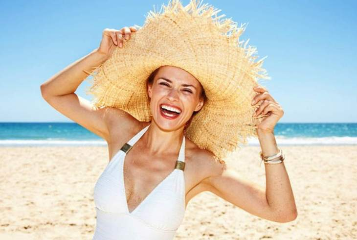 Smilling woman in swimsuit playing with big straw hat | Hydrate Yourself Happy With Alkaline Water!