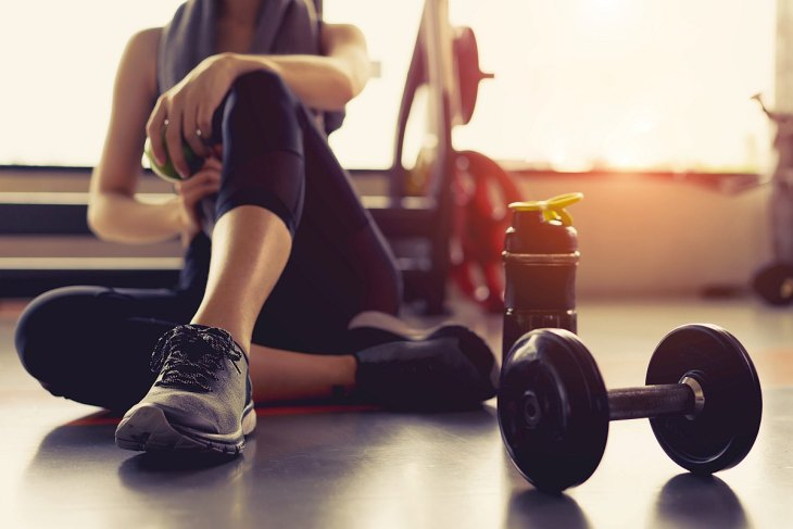 Woman taking a break in the gym | The Importance Of Good Hydration When Working Out
