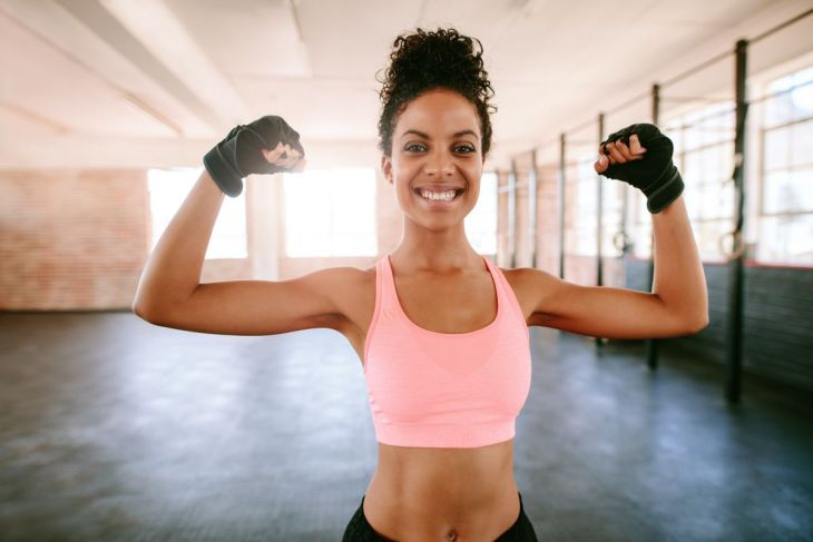 woman flexing arms | Alkaline Water Benefits For Your Skin, Hair, And Health | alkaline water benefits for health