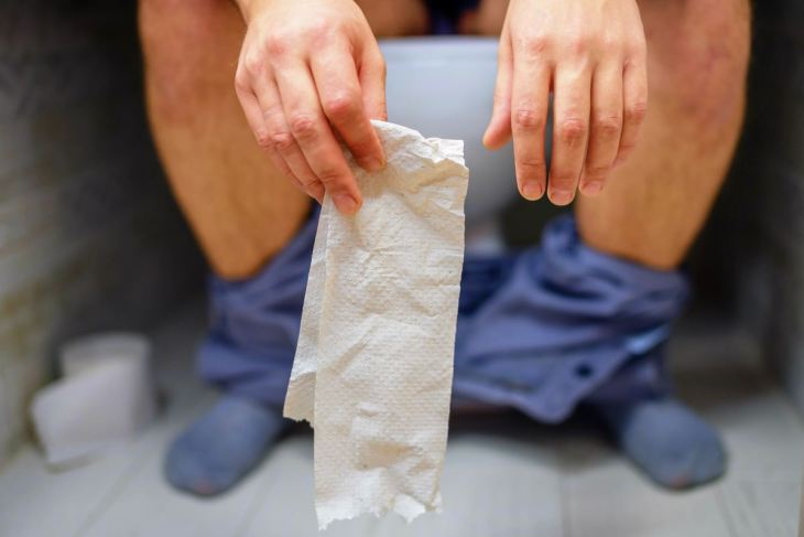 man holding tissue paper | Why You Should Manage Your Fluid Intake To Treat Constipation | recommended fluid intake