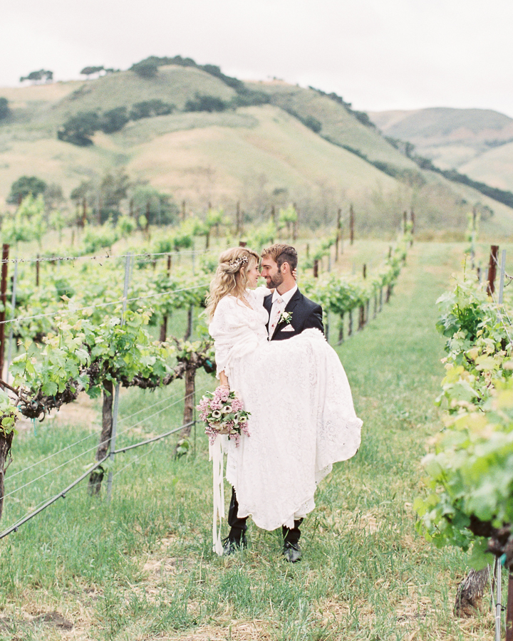 a groom carries his wife after their wedding at Higuera Ranch