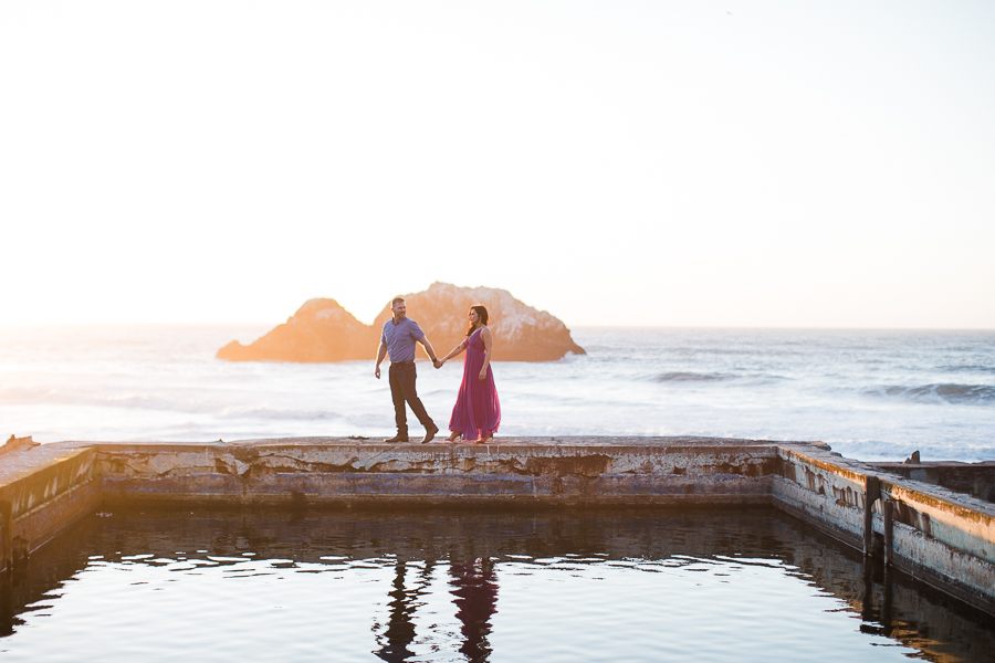 a couple walks around the baths walls during engagement photos at Sutro Baths