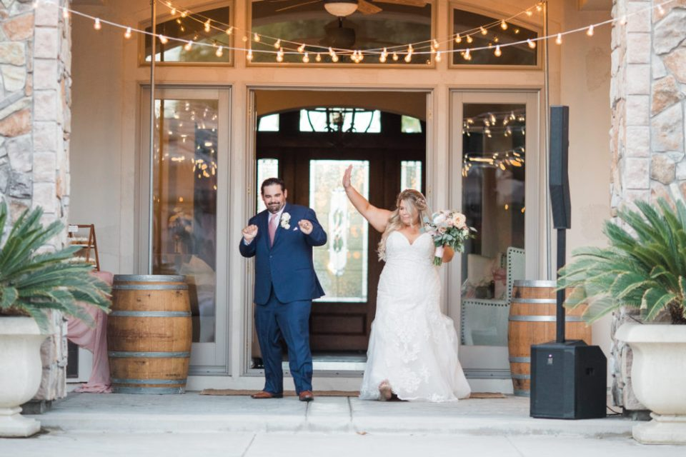 bride and groom celebrate their entrance to their intimate estate wedding reception