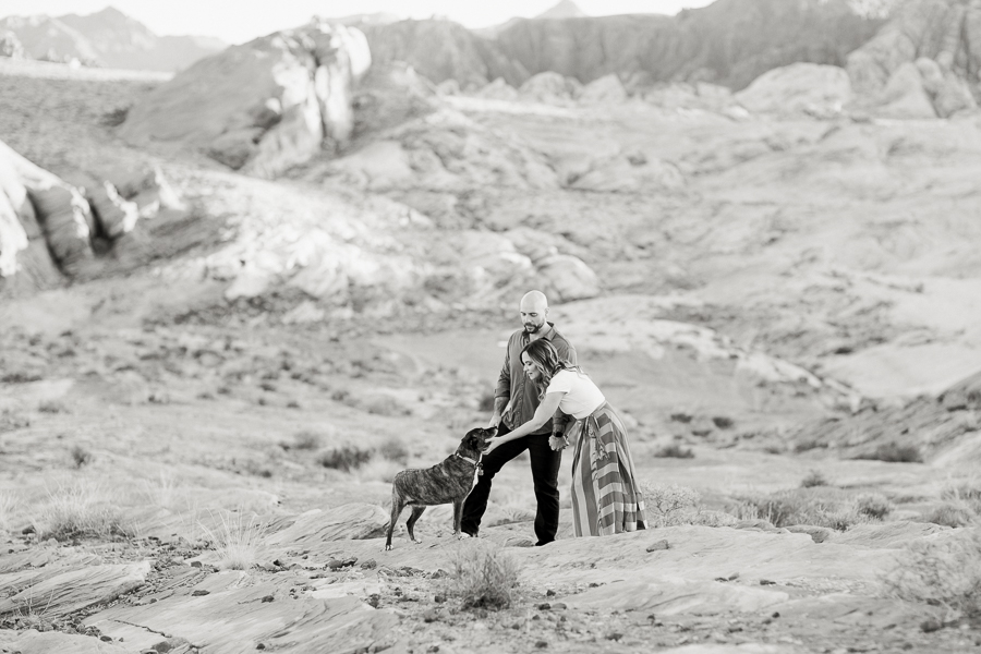 black and white photo of a couple playing with their dog during Valley of Fire engagement session