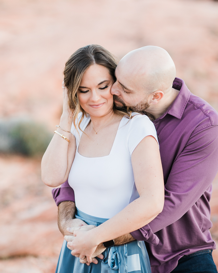 a man hugs his fiancee from behind during Valley of Fire engagement session