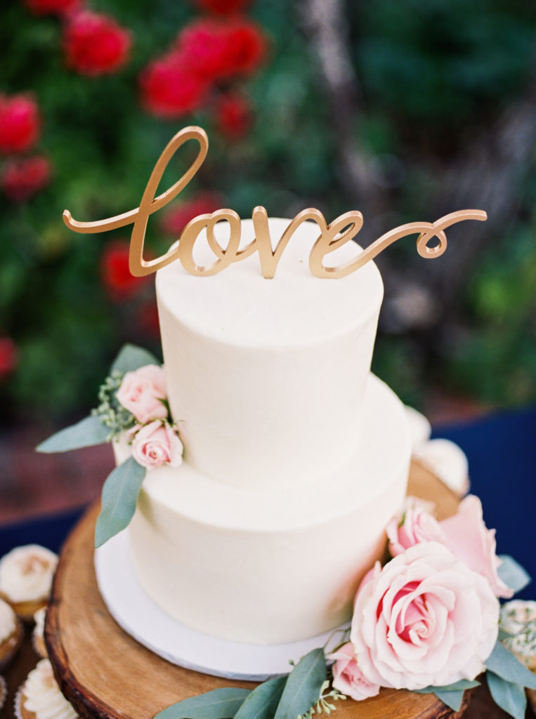 white wedding cake with love cake topper