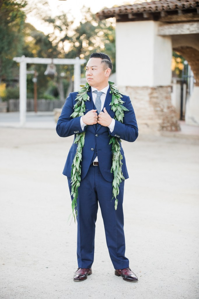 groom poses with his wedding lei