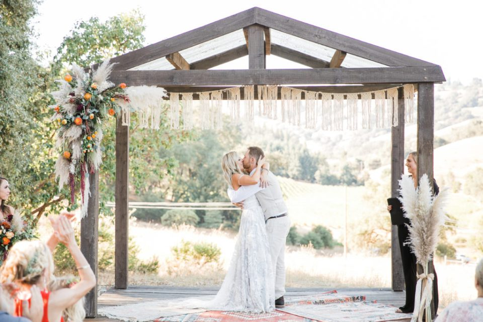 bride and groom sharing a first kiss in a beautiful ceremony area designed by a wedding planner