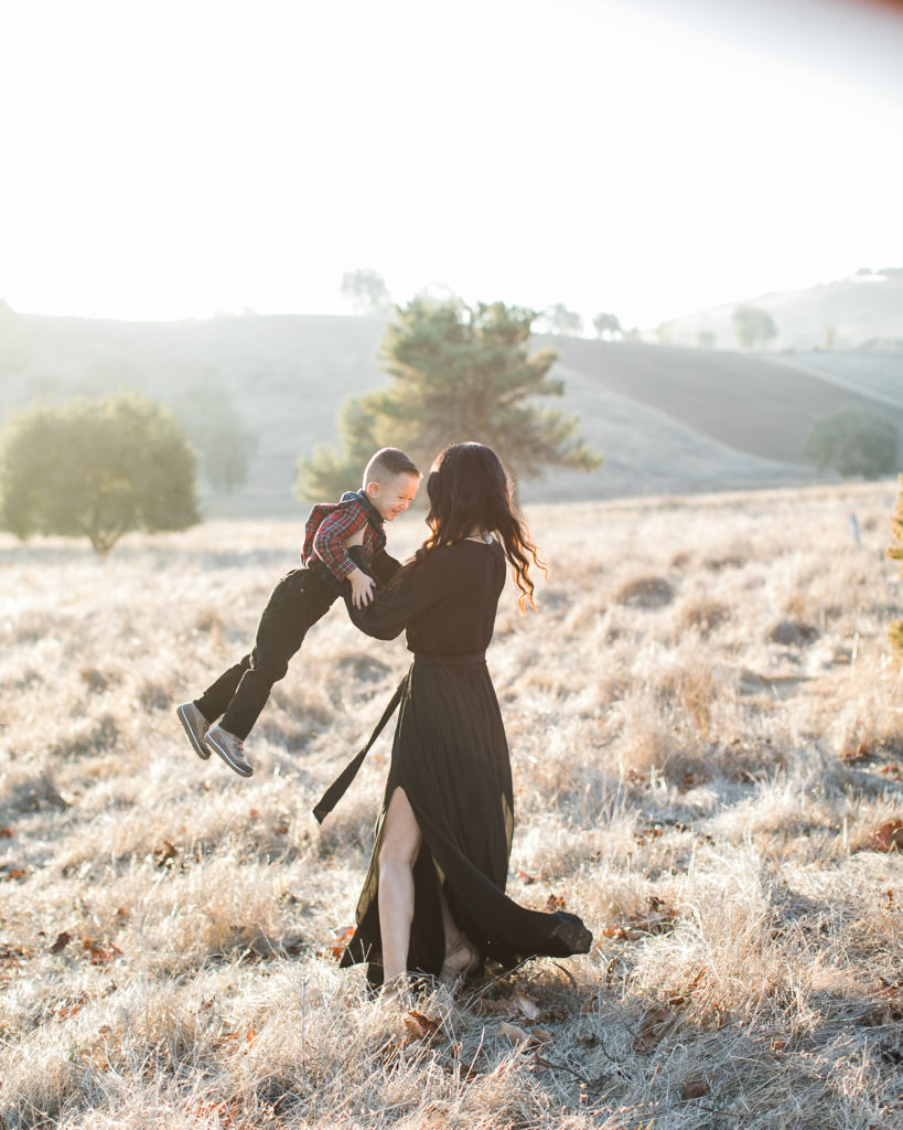 mom swings son around during family photos at Santa Teresa Park