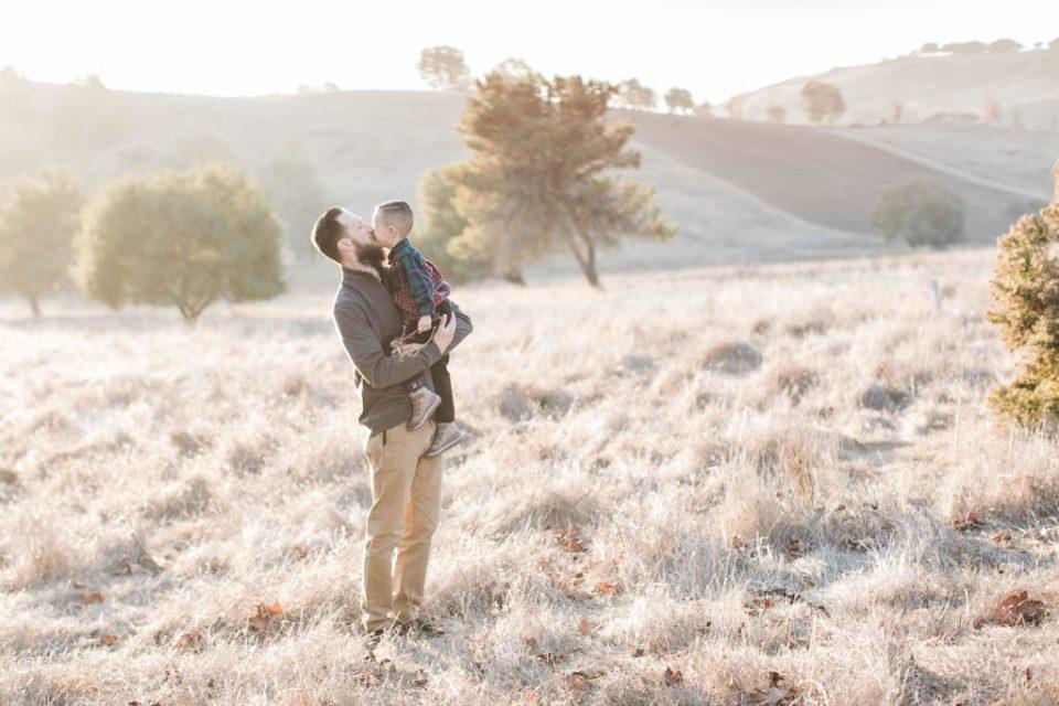 son gives dad a kiss during family photos at Santa Teresa Park