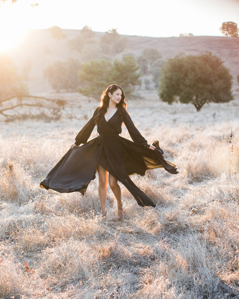a woman twirls in the field during family photos at Santa Teresa Park