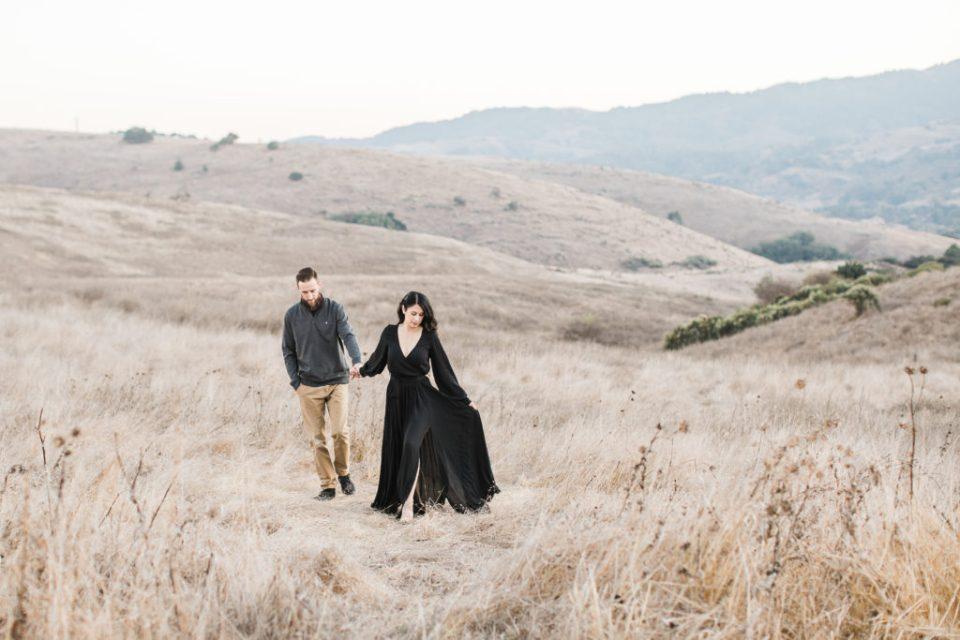 a couple walks up a hill during family photos at Santa Teresa Park