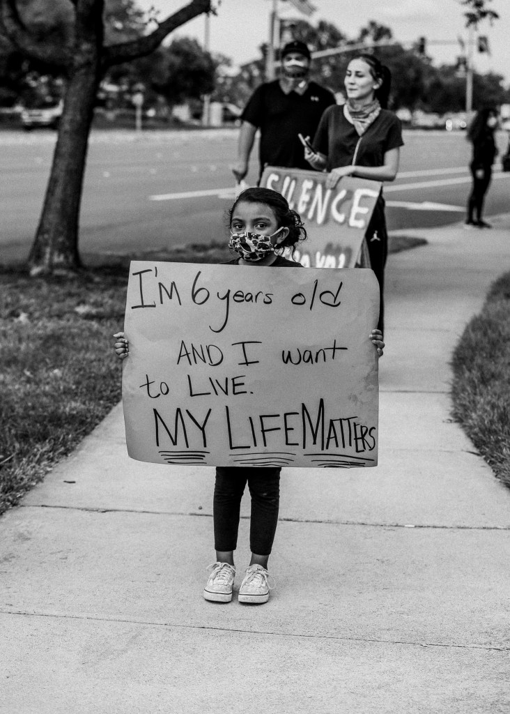 child carrying a sign during a peaceful protest in Tracy, CA
