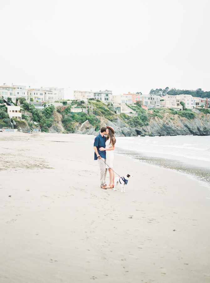 a couple and their dog pose for photos on the beach for a post about tips for beach photos